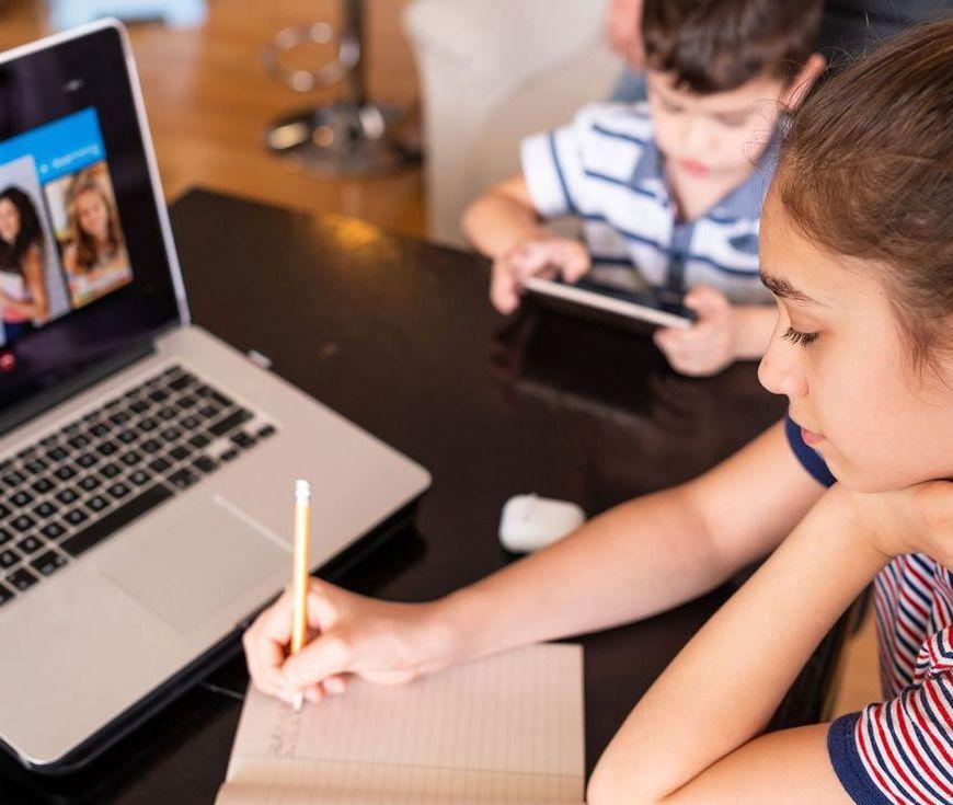 Unha nena seguindo unha clase online e tomando apuntes